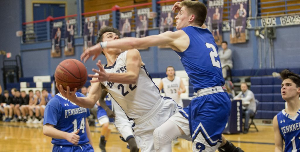 Zac Manoogian of Westbrook gets fouled by Kennebunk's Zack Sullivan but still makes the shot Friday night in a Class A basketball game in Westbrook. Manoogian scored 24 points, leading the Blue Blazes to a 64-38 win.