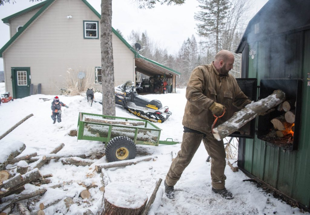 James Black loads logs into his wood-burning furnace, the main heating source for his home in Wilton. Black also has a wood lot with timber he has made available on an emergency basis.
