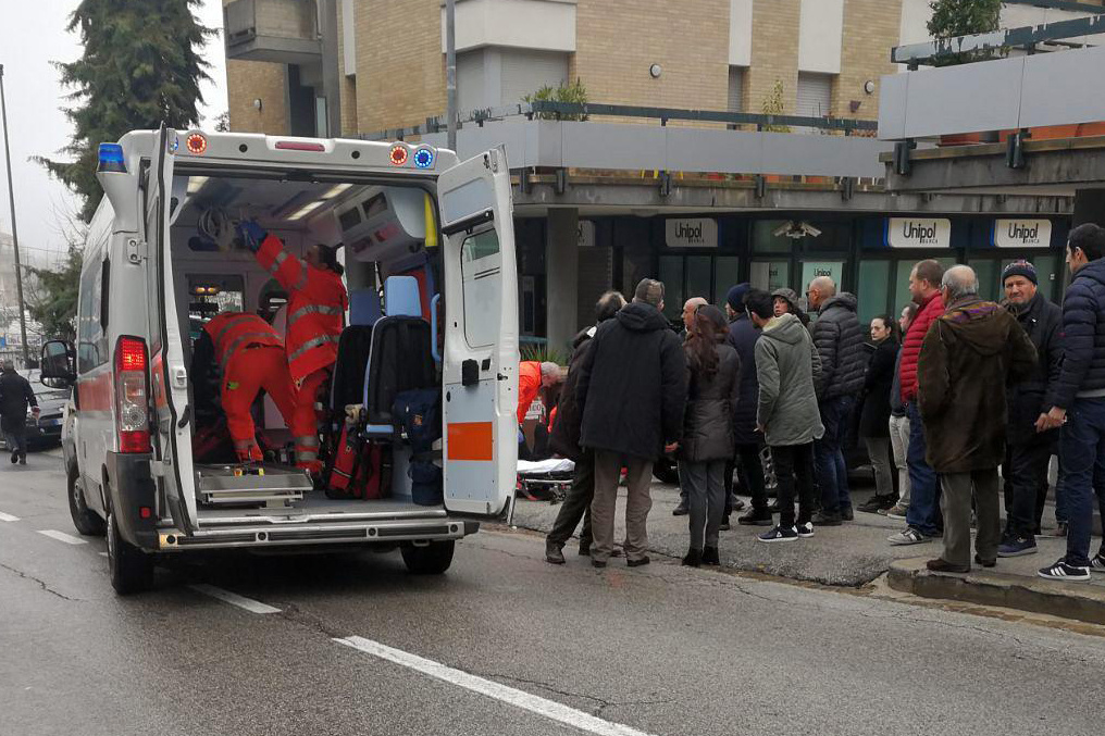 Paramedics aid one of the six people of African descent wounded in a string of drive-by shootings Saturday in Macerata, Italy.