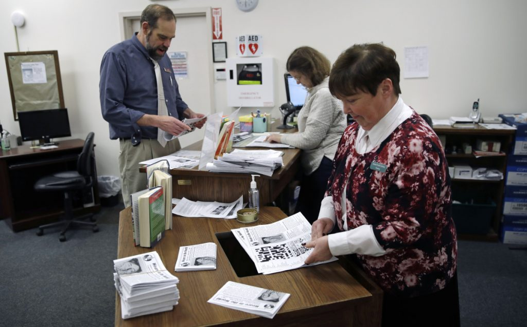 Librarian Thelma Tracy, right, folds editions of the Weare in the World with her co-workers at the public library in Weare, New Hampshire, last month.
