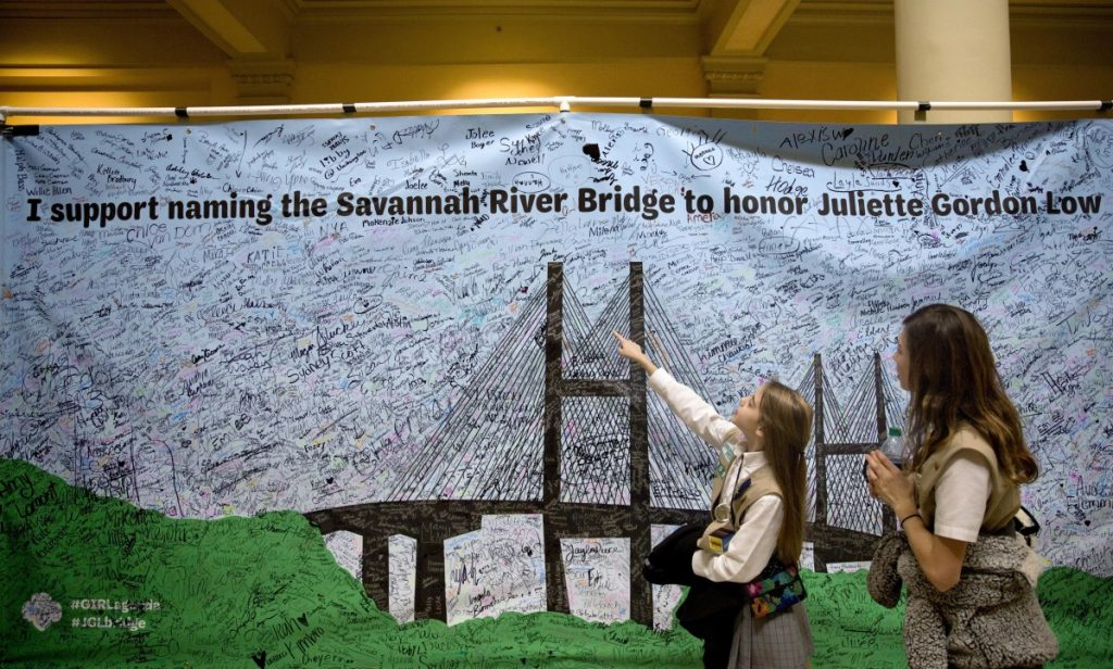 Two Girl Scouts pass by a banner Tuesday at the Georgia Capitol aimed at persuading legislators to name a local bridge after the organization's founder. The bridge is now named for segregationist former Gov. Eugene Talmadge.