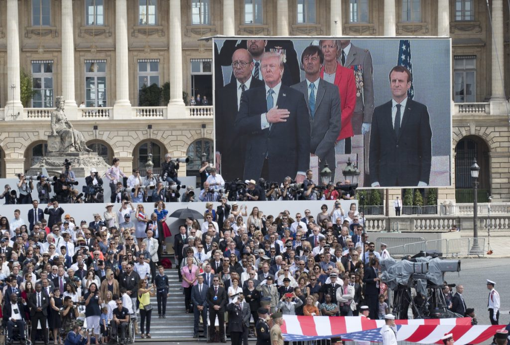 President Trump and French President Emmanuel Macron are seen on a large screen as the Stars and Stripes passes during France's military parade on Bastille Day in Paris last July.