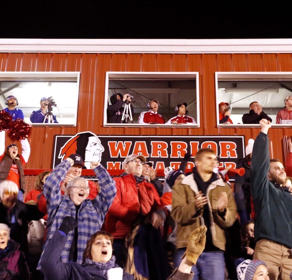 Wells High School fans cheer in front of a press box with a logo of a Native American during a football game last fall. A letter writer says the logo is a generic symbol that is treated with reverence and respect.=