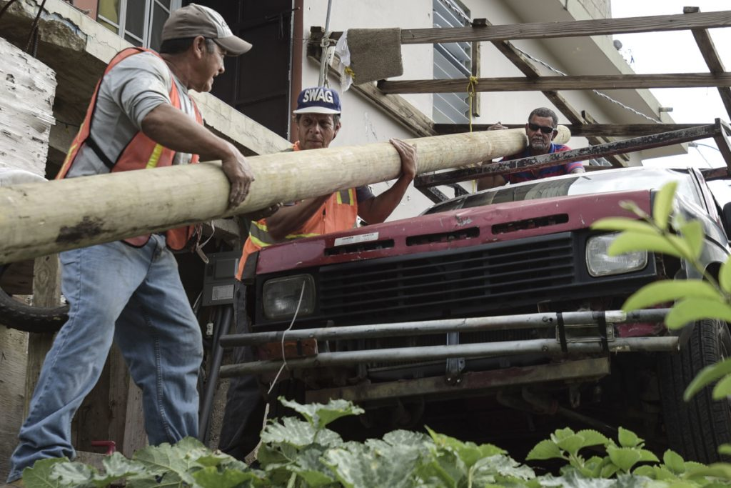 Retired carpenter Felipe Rodriguez, far right, uses his truck to help municipal workers, who are also local residents, move a power pole so they can install it near his home. Rodriguez also has no water but receives bills for services he's not getting.