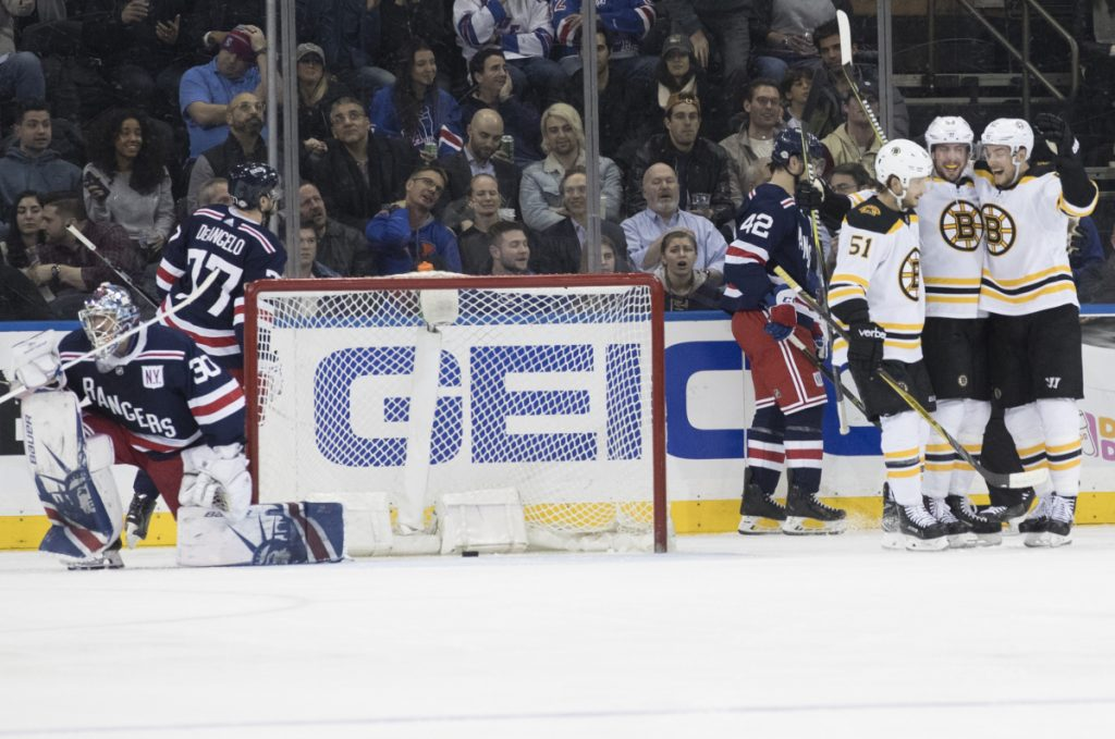 Rangers goaltender Henrik Lundqvist gets up as Bruins center Tim Schaller, second from right, celebrates his goal during the second period Wednesday night in New York.