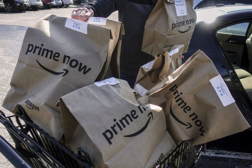 Amazon Prime Now bags full of groceries are loaded for delivery by a part-time worker outside a Whole Foods store in Cincinnati, where deliveries started Thursday.
