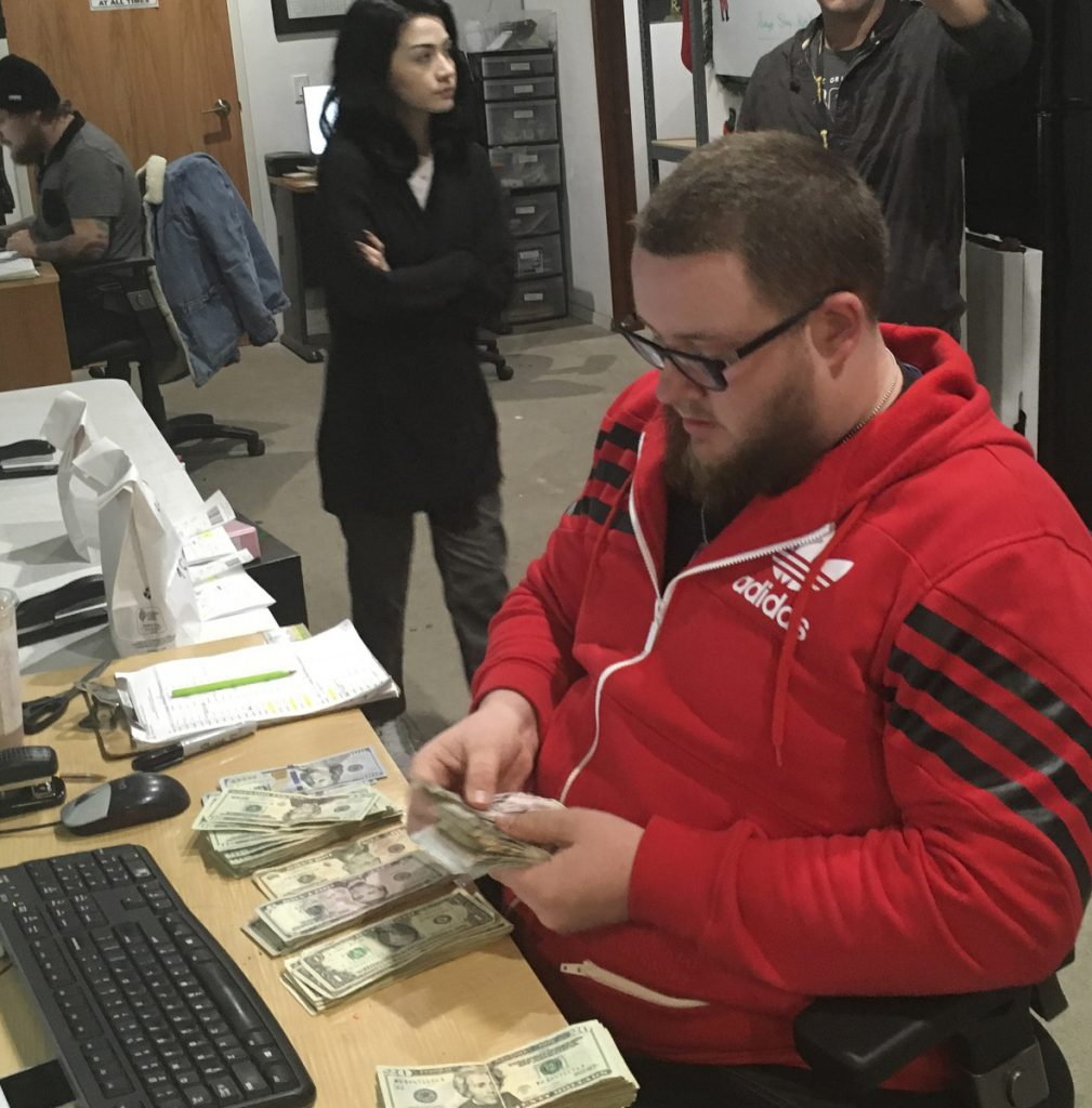 Employee Joshua Wilson counts cash at the Golden State Greens marijuana dispensary in San Diego.