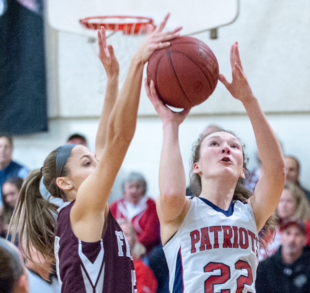 Megan Cormier of Freeport blocks a shot by Gray-New Gloucester's Jordan Grant, who finished with 26 points to lead the Patriots to a 52-43 win Thursday night. (Russ Dillingham/Sun Journal)