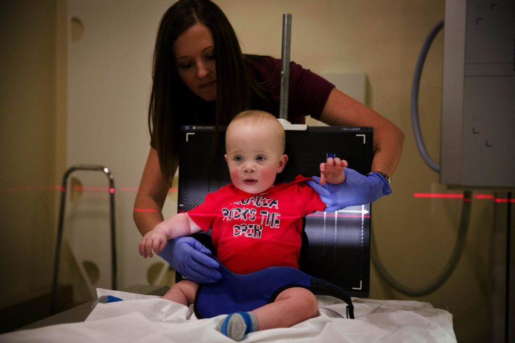 Kilian Daugherty, 1, is prepped for a chest X-ray by radiology technologist Kerah Adams while he's examined for flu symptoms at Upson Regional Medical Center in Thomaston, Ga., on Friday, as the flu further tightens its grip on the U.S.
