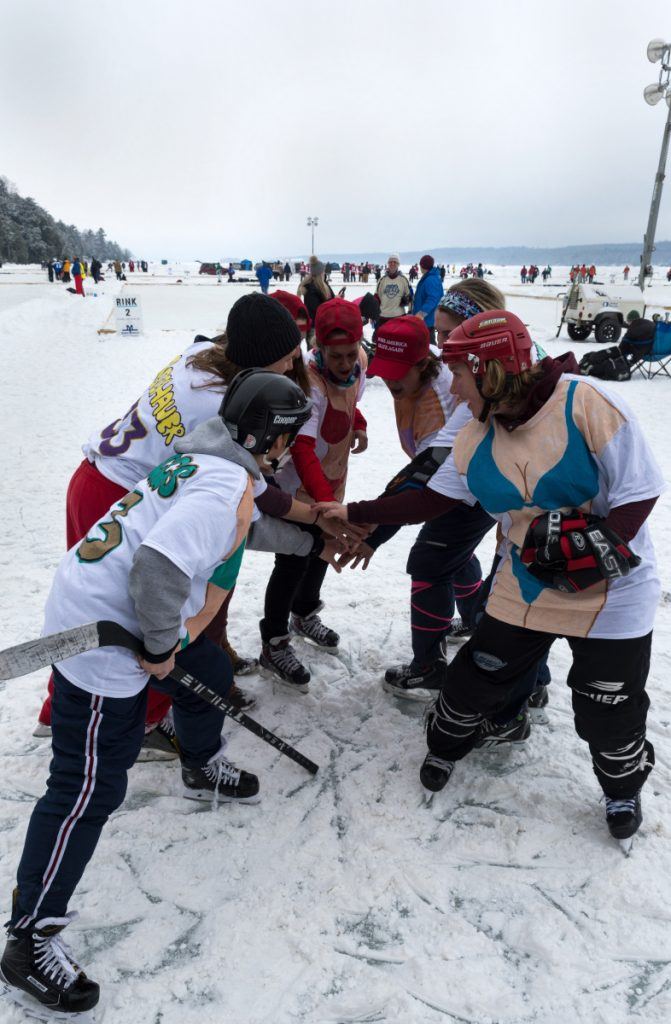 The all-female hockey team Box Fourmation, made up of rowdy former college athletes, huddles at the 2018 Maine Pond Hockey Classic on Messalonskee Lake in Sidney.