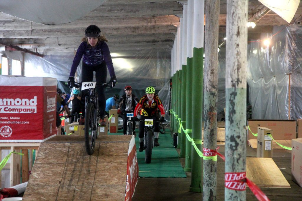 """Competitors take part in an indoor mountain bike race inside the old American Woolen Mill in Vassalboro on Sunday. The race was a fundraiser for the """"Save the Mill"""" campaign and was organized by the Central Maine Cycling Club."""