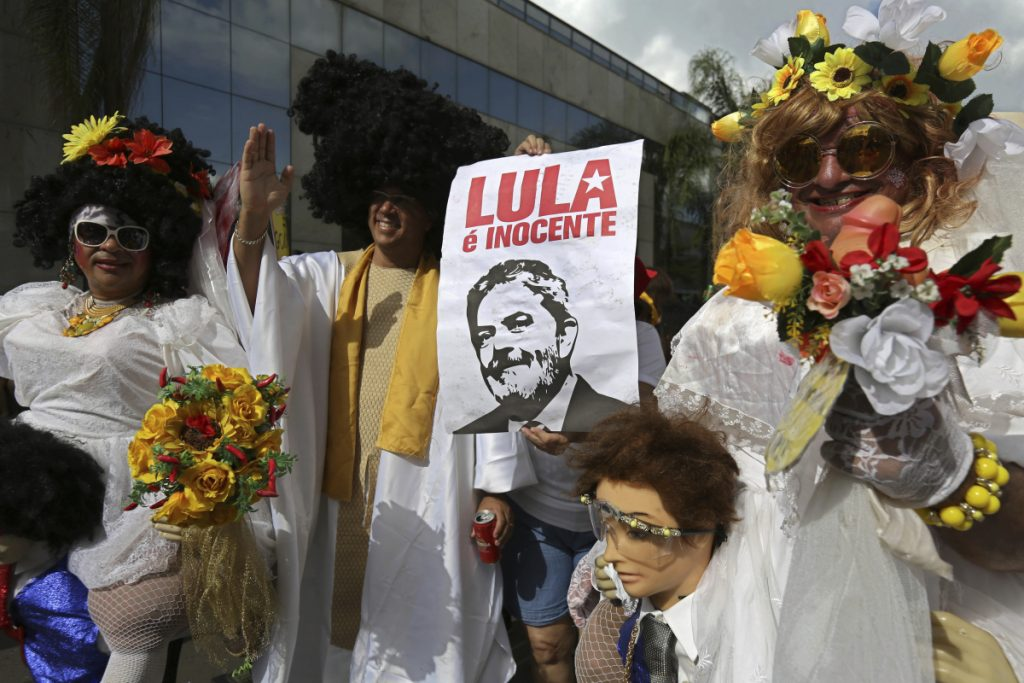 "Revelers in white costumes carry an image of Brazil's former President Luiz Ignacio Lula da Silva below the Portuguese phrase ""Lula the Innocent"" during the Pacotao street carnival party in Brasilia, Brazil, Sunday. Lula faces a growing risk of being arrested within weeks after a corruption conviction."