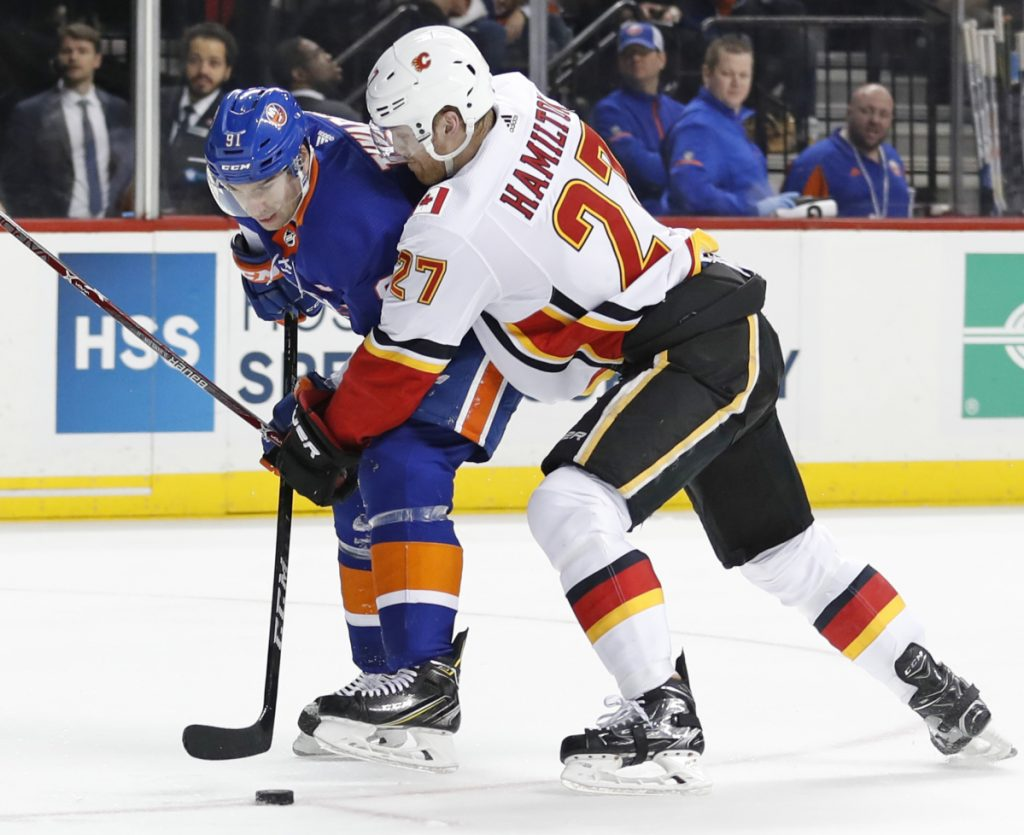 Dougie Hamilton of the Calgary Flames attempt to check John Tavares of the New York Islanders off the puck Sunday night. Calgary won, 3-2.