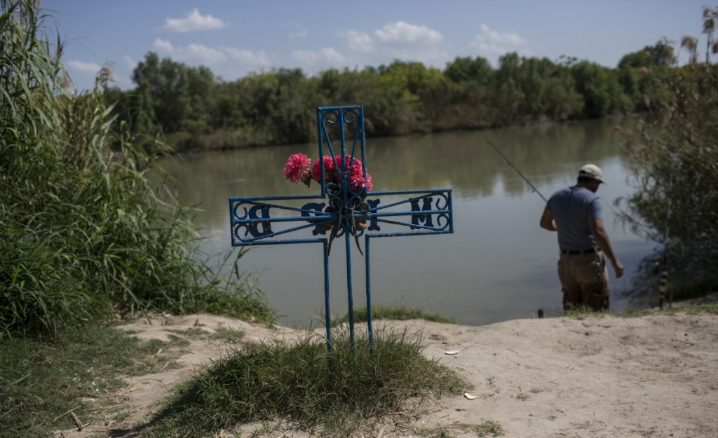 A man fishes in the Rio Grande near a memorial for a migrant who died while trying to cross the river from Tamaulipas state, Mexico, into the U.S. through Laredo, Texas. Maine students who travel to the border to assist immigrant detainees hear emotional stories of trauma.