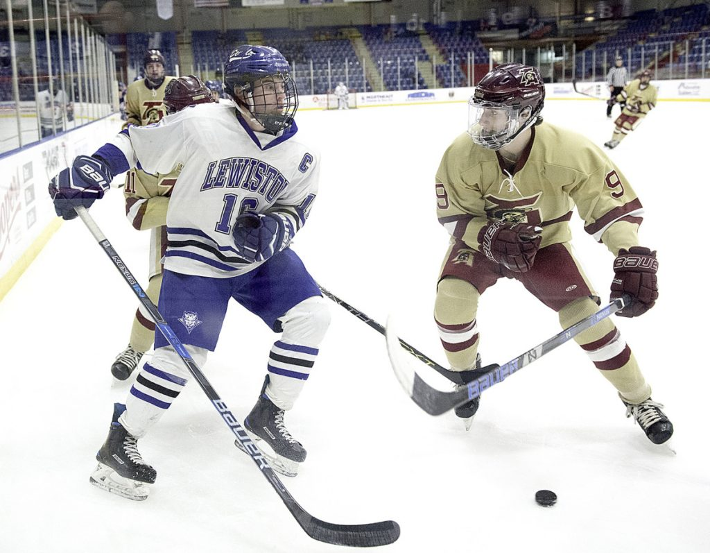 Owen Dubois, right, of Thornton Academy lowers his shoulder before checking Alex Robert of Lewiston during the first period of Lewiston's 2-1 victory Monday night.