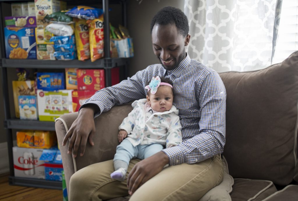 Douglas Rutamu and his 4-month-old daughter, Zahra, at their home in Portland. Rutamu and his partner, Jessica Morse, started the delivery service Snacks on Snacks in January. The service mostly delivers candy, but can also bring items like diapers and formula.