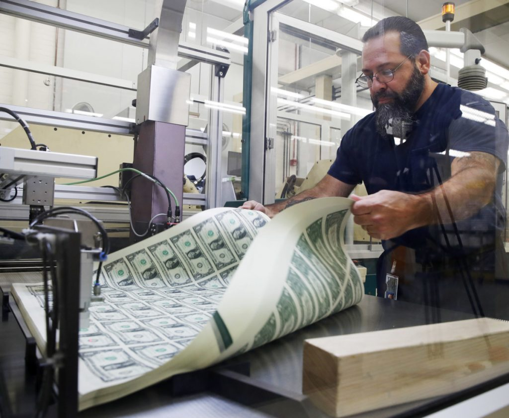Vincent Tacconelli aerates sheets of dollar bills on Nov. 15. Most economists expect inflation to edge up and end the year a few tenths of a percentage point above the Federal Reserve's target.