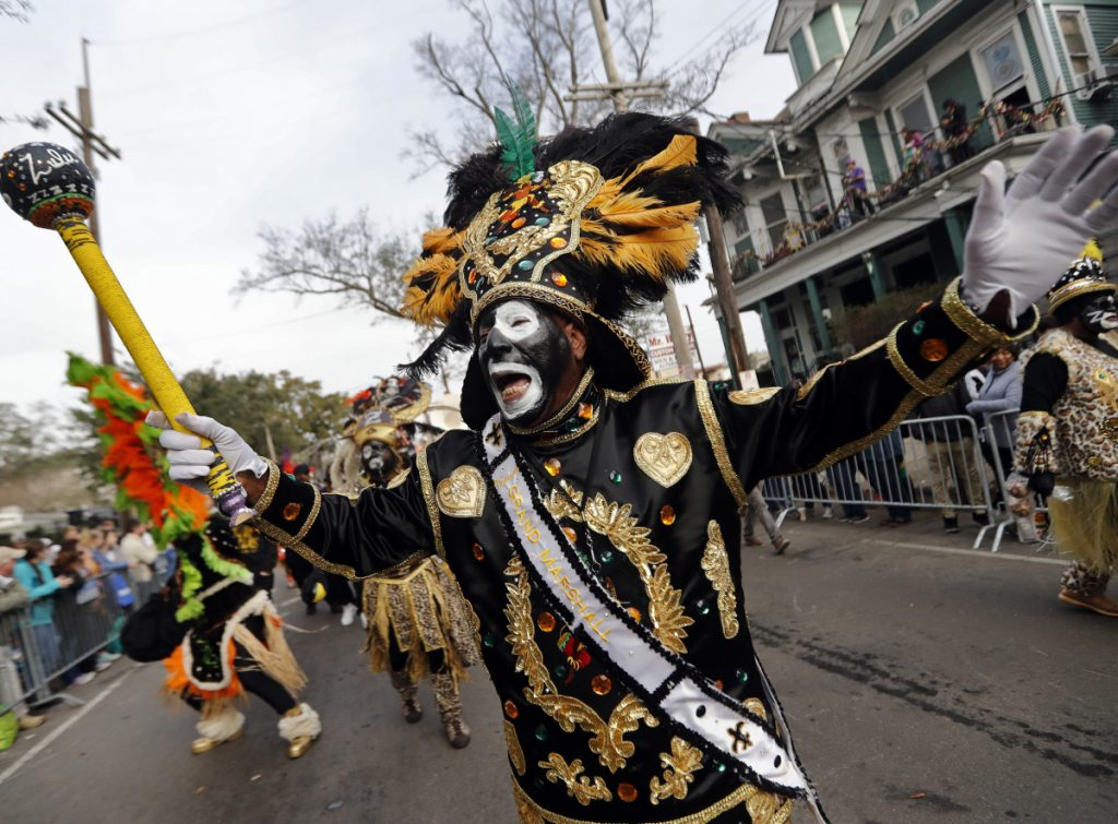 A member of the Krewe of Zulu marches during Mardi Gras parade day in New Orleans, Tuesday.