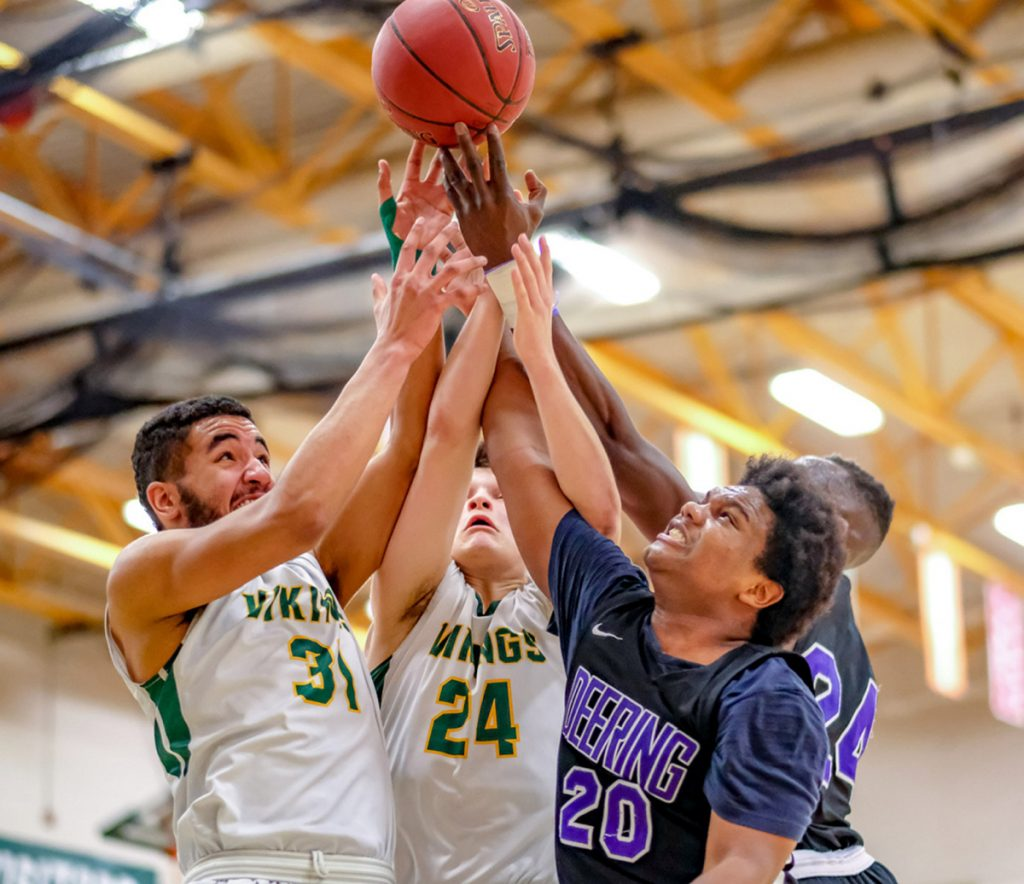Oxford Hills' Atreyu Keniston, left, and Janek Luksza battle for a rebound with Deering's Darryl Germain, front, and Ben Onek in Wednesday night's Class AA North quarterfinal at Paris.