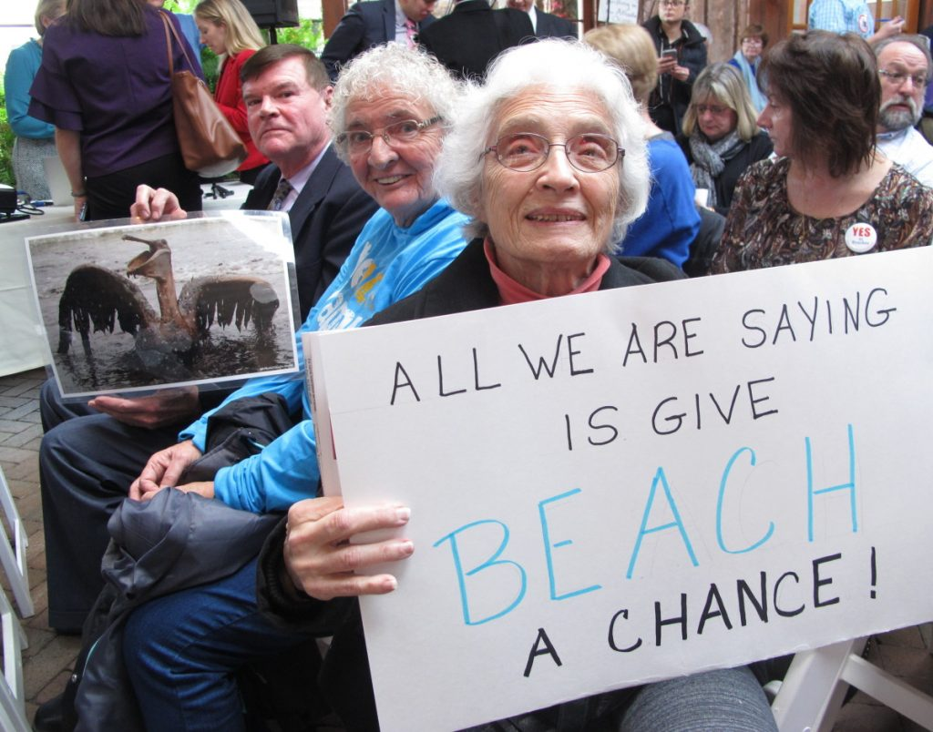 People hold signs protesting President Trump's plan to allow offshore oil and gas drilling along both of the nation's coasts during a hearing Wednesday in Hamilton, N.J. The public is not allowed to speak to attendees at the meetings and are asked to type comments on laptops provided by the Bureau of Ocean Energy Management.