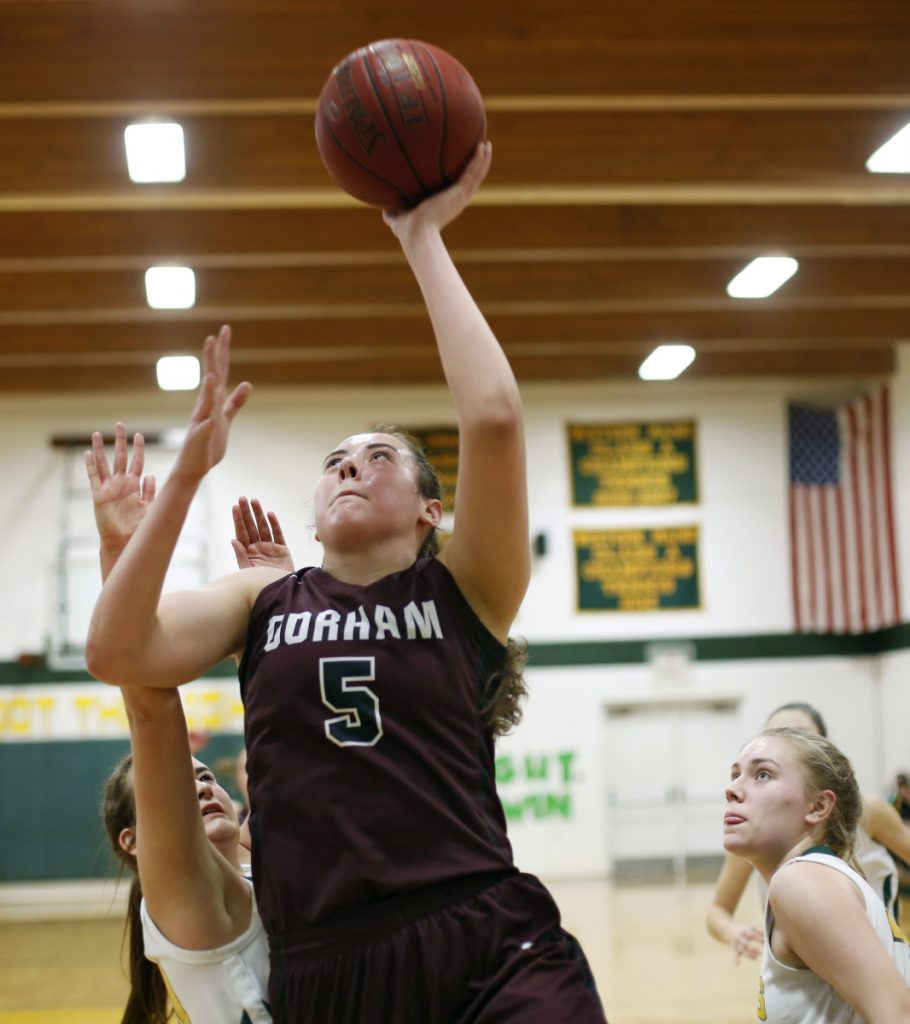 Mackenzie Holmes, who scored 21 points Thursday for Gorham, finds room between Madison Legassey, left, and Katie Fitzpatrick of Maine Girls' Academy.