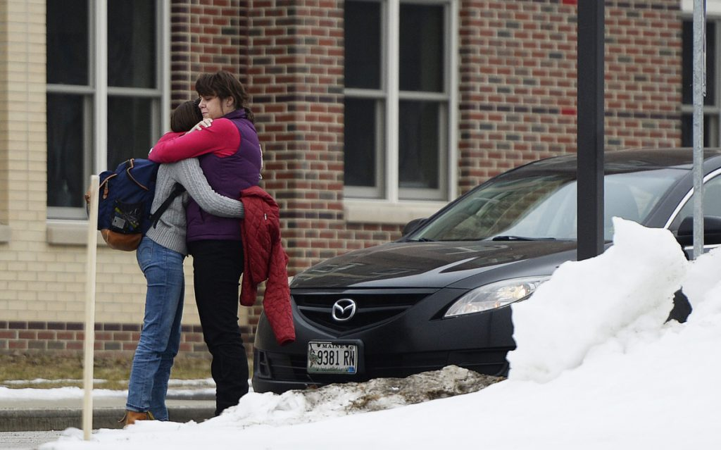 "Robin Davis hugs her daughter Caroline, a sophomore, as she picks her up Thursday at South Portland High School. Earlier in the day, a 15-year-old student on his way to school was arrested on a charge of terrorizing after allegedly posting a social media message about ""shooting up the school."""