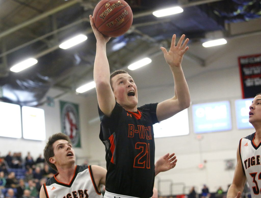 Sam Sharpe of Brunswick drives to the basket between Carter Edgerton, left, and DeSean Cromwell of Biddeford during their Class A South quarterfinal Saturday night at the Portland Expo. Biddeford won, 50-48.