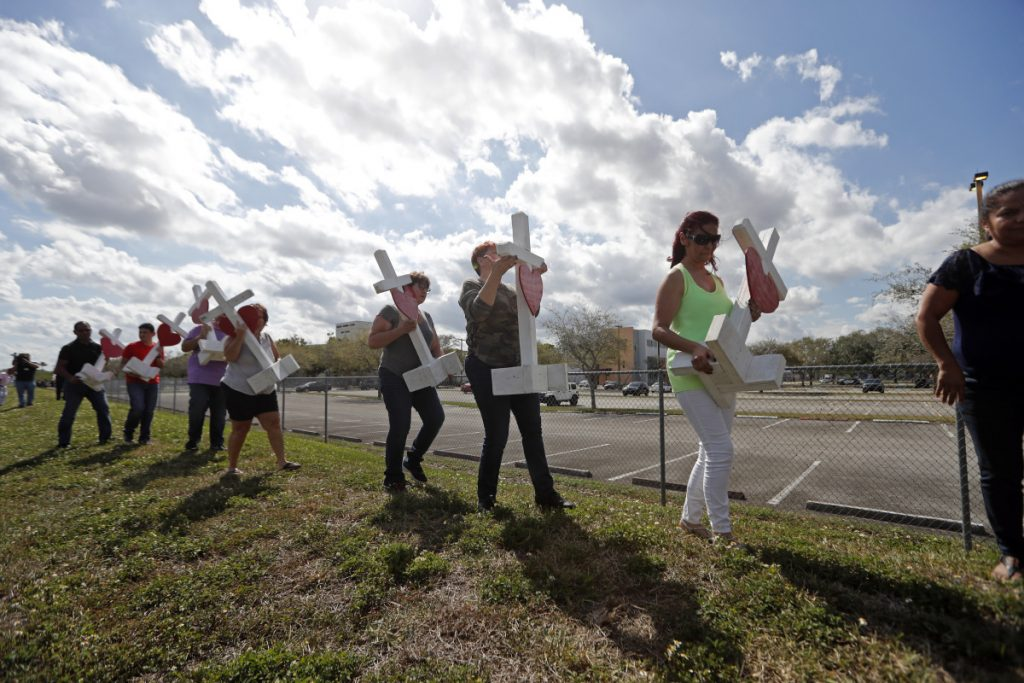 Volunteers carry 17 crosses to be placed outside the Marjory Stoneman Douglas High School in Parkland, Fla., on Sunday, where 17 people were killed in a mass shooting Wednesday, allegedly by former student Nikolas Cruz.