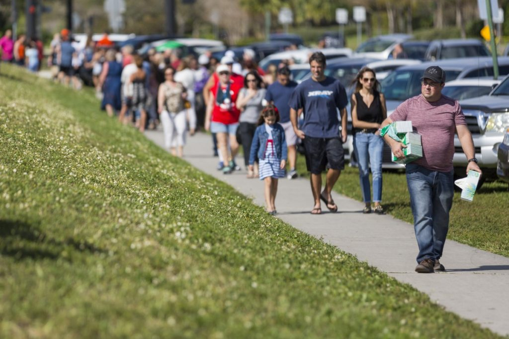 Chris McCormick, far right, from First Priority of South Florida, carries boxes of tissues for grieving community members outside of Marjory Stoneman Douglas High School in Parkland, Fla., on Sunday.
