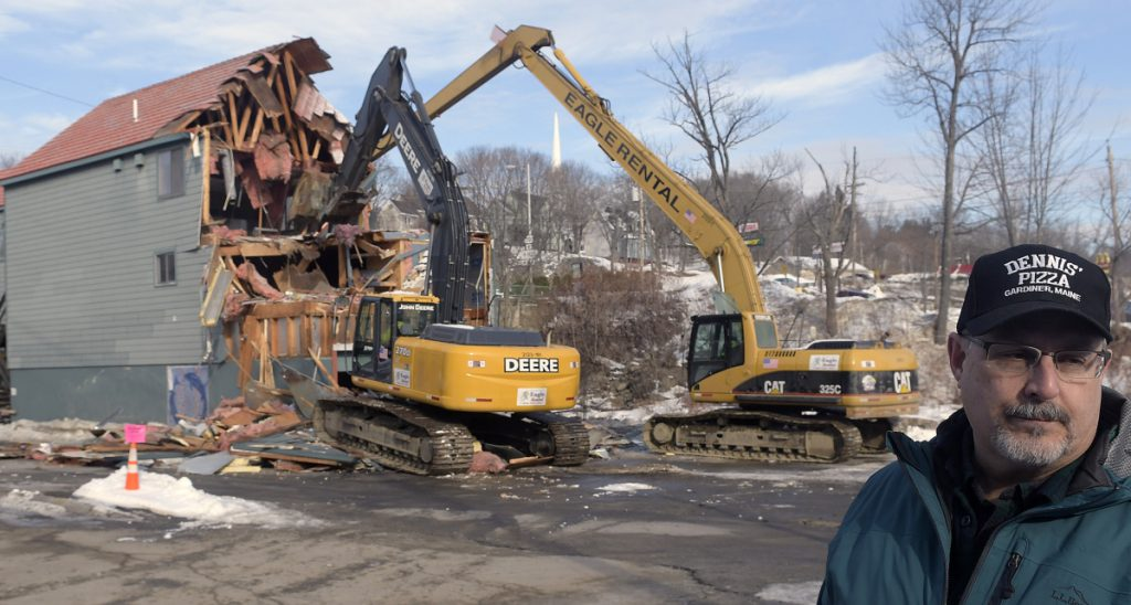 "Dennis Wheelock watches demolition crews raze his former business, Dennis' Pizza, in Gardiner on Monday. ""Thirty years to build it; one day for it to come down,"" Wheelock said."