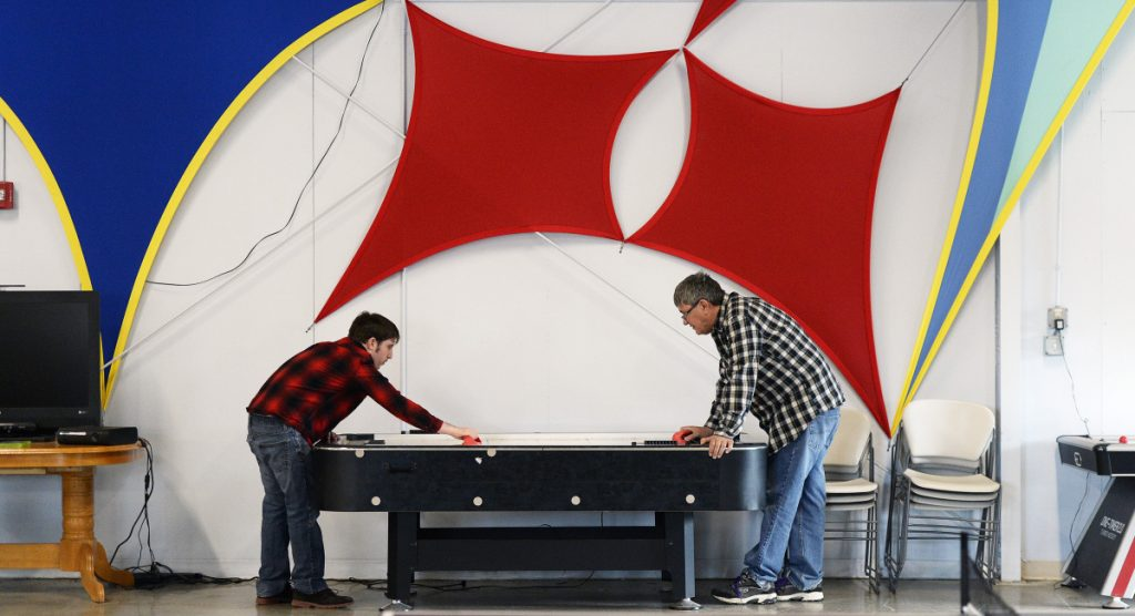 David Conrad, right, of PSL Services/STRIVE plays air hockey with Brendan Young, who has intellectual disabilities, as part of a program at STRIVE. Young's mother said that when the group home her son stays at in Windham has a run of stable, quality employees, he thrives.