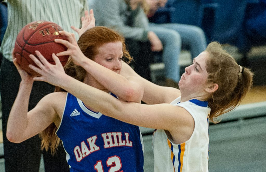 Lake Region High's Rachel Shanks pressures Oak Hill's Sadie Waterman in the backcourt during Tuesday's Class B South girls' basketball quarterfinal at the Portland Expo. (Russ Dillingham/Sun Journal)