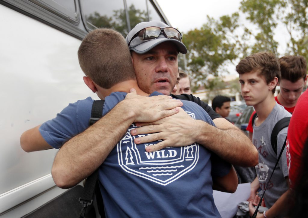Tom Carmo, father of survivor Ethan Rocha, hugs student Joey Cordova, as students from Stoneman Douglas High School board buses in Parkland, Fla., Tuesday. The students plan to hold a rally Wednesday in hopes that it will put pressure on the state's Republican-controlled Legislature to consider a sweeping package of gun-control laws.