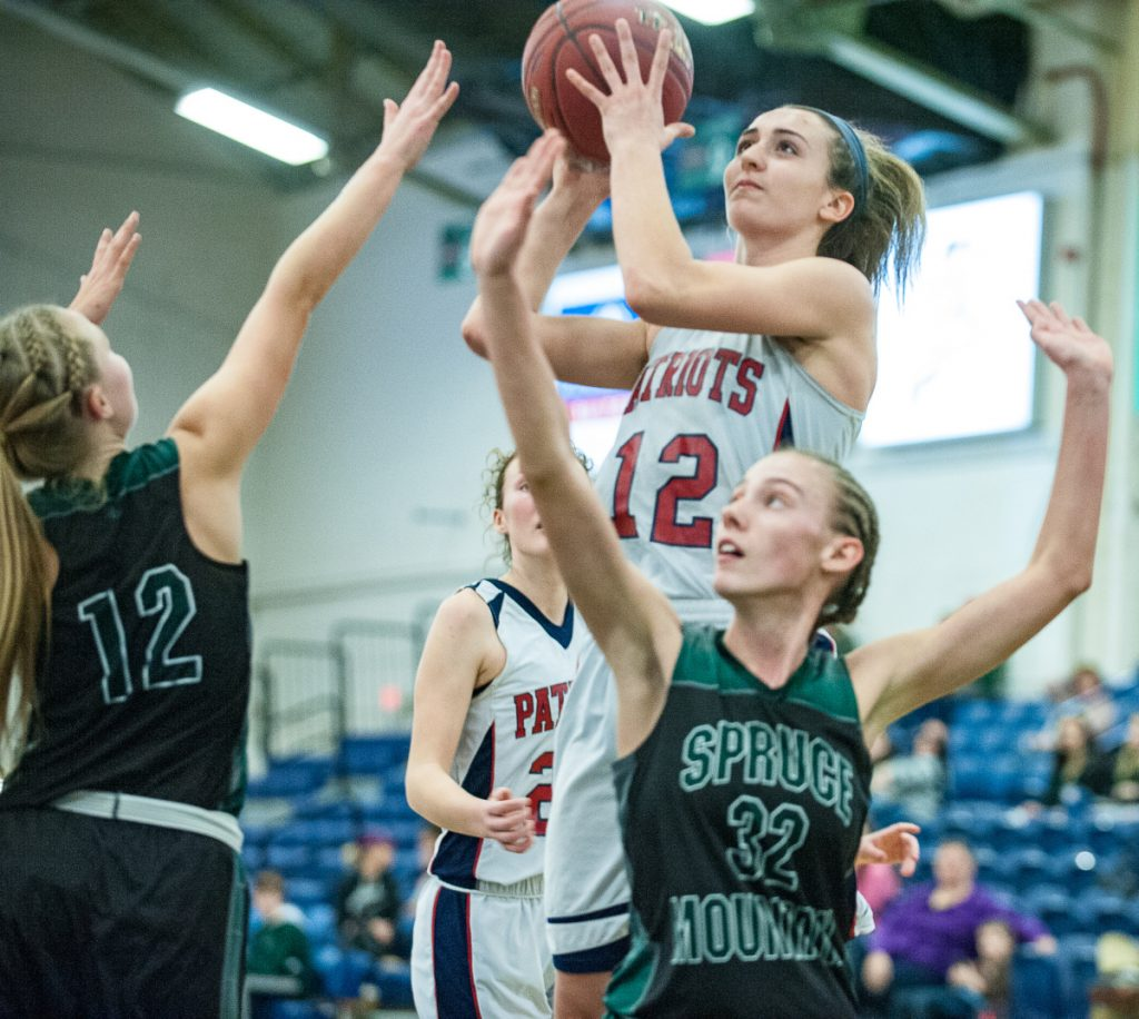 Bri Jordan drives to the basket over Spruce Mountain's Calley Baker, right and Morgan Dalton during Tuesday's 49-34 victory. The Patriots outscored the Phoenix 26-16 in the second half.
