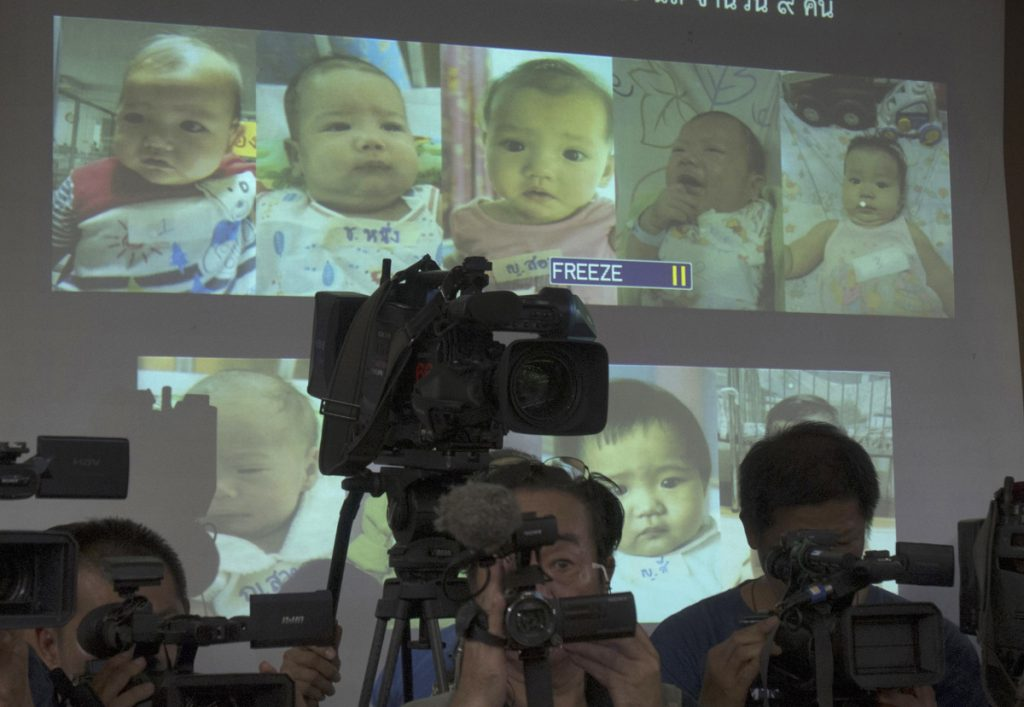 Thai police display pictures in 2014 of babies born to a Japanese man through surrogacy.