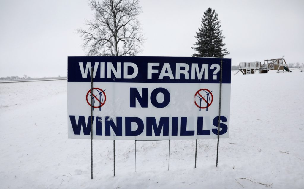 An anti-wind turbine sign stands in the front yard of a farmhouse on Jan. 24 in Glenville, Minn. Opponents of wind power are successfully stalling or rejecting wind-farm projects across the country.