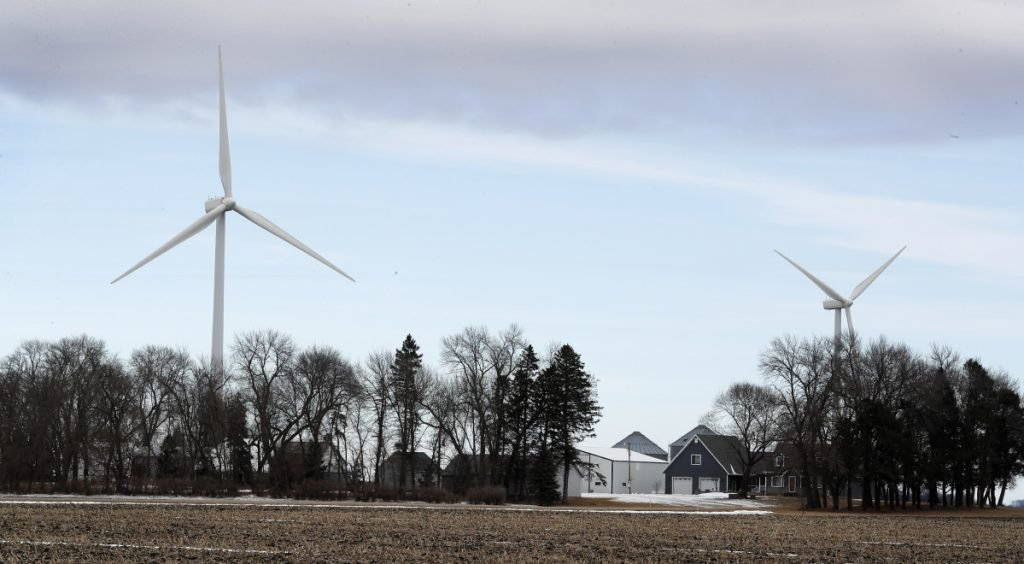 Turbines tower over a farmhouse near Northwood, Iowa. A newly invigorated rebellion against wind power is raising a host of anti-wind ideas.