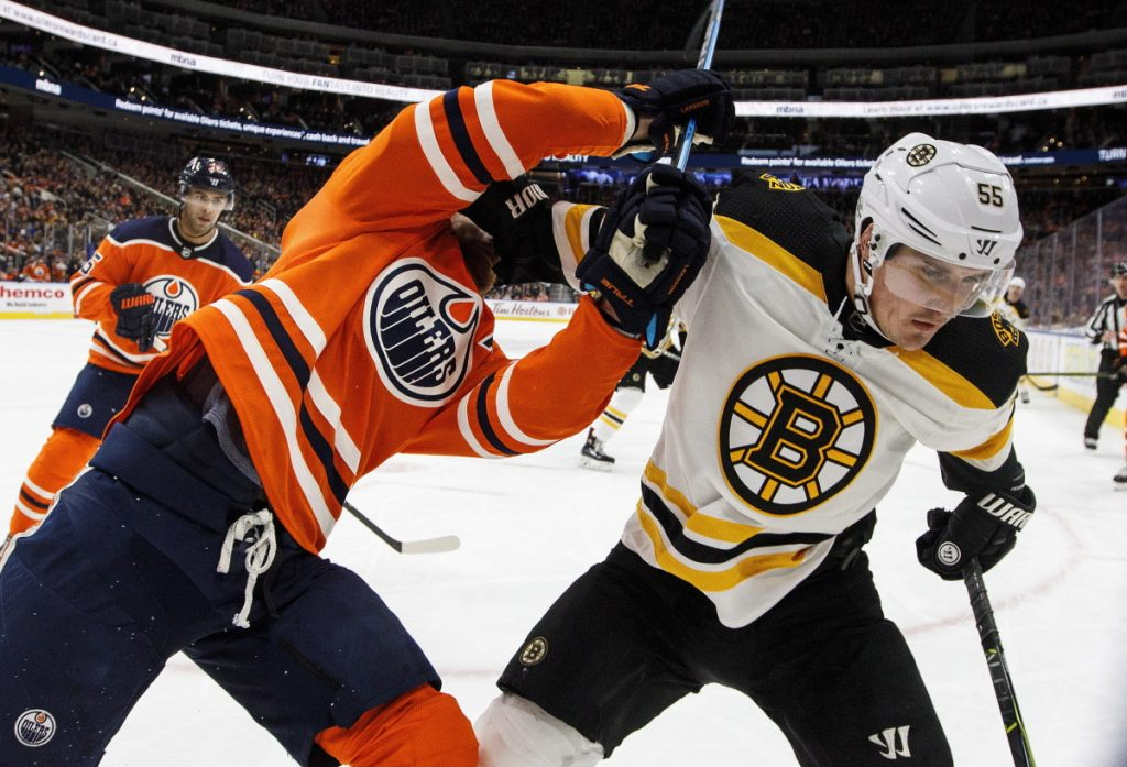 Boston Bruins' Nick Holden and Edmonton Oilers' Adam Larsson  battle in the corner during the third period of the game on Tuesday in Edmonton.