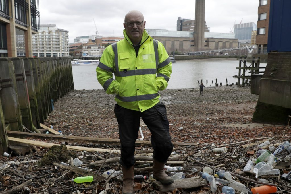 "Michael Byrne, a ""data gatherer,"" stands amid plastic bottles and other debris Friday that had washed up on the bank of the River Thames in London."
