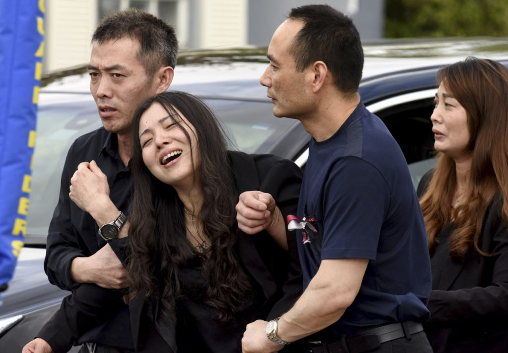 Peter Wang's mother, Hui, cries as she is helped into a waiting car with her family after the memorial service for her 15-year-old son at Kraeer Funeral Home in Coral Springs, Fla., on Tuesday. Peter Wang was among the victims in the massacre at Marjory Stoneman Douglas High School in Parkland, Fla., last week.