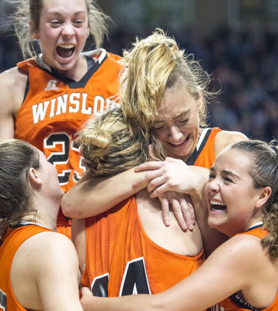 Haley Ward of Winslow jumps into the arms of teammate Weslee Littlefield after the Black Raiders won the Class B North title Saturday with a 43-39 overtime victory against Presque Isle at Cross Insurance Center.