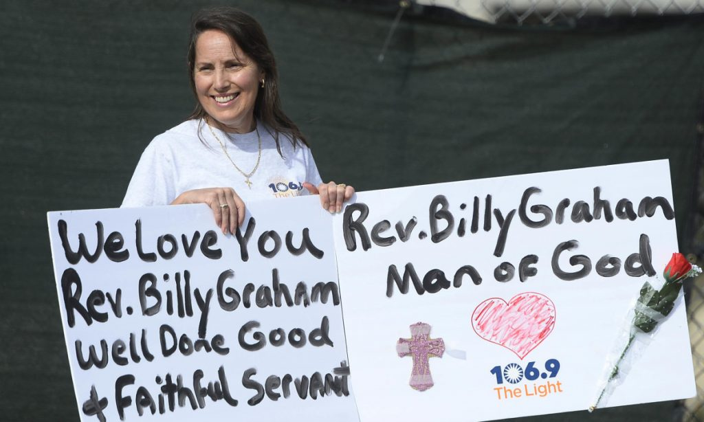Rose Salazar of Cornelius, N.C., waits for the motorcade carrying the body of the late Rev. Billy Graham to proceed through uptown Charlotte, N.C. on Saturday.