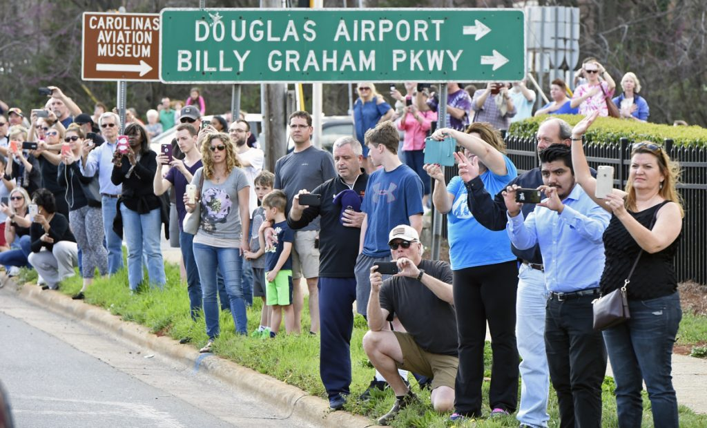 People take photos as the hearse carrying the body of Billy Graham drives toward Charlotte, N.C., on Saturday.