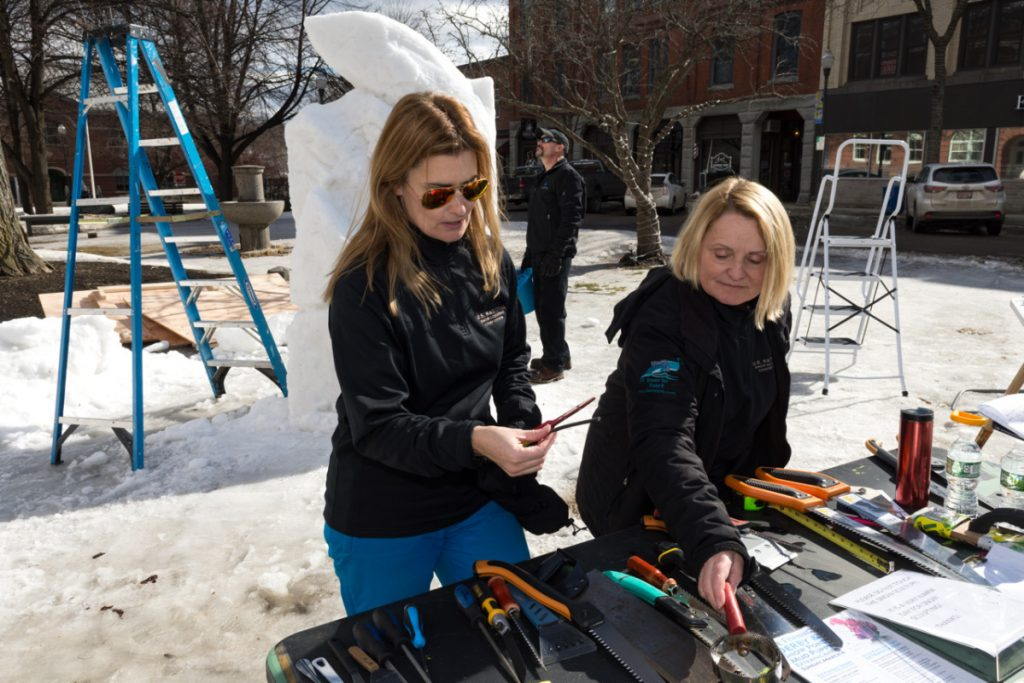 Amanda Bolduc, left, and her mother, Cathy Thompson, discuss tools of their trade, while Chris Thompson, center, tends to their snow sculpture. This is Chris Thompson's first year in snow sculpting, following in his mother and sister's footsteps. He said he hadn't played in the snow with his family since he was a boy.