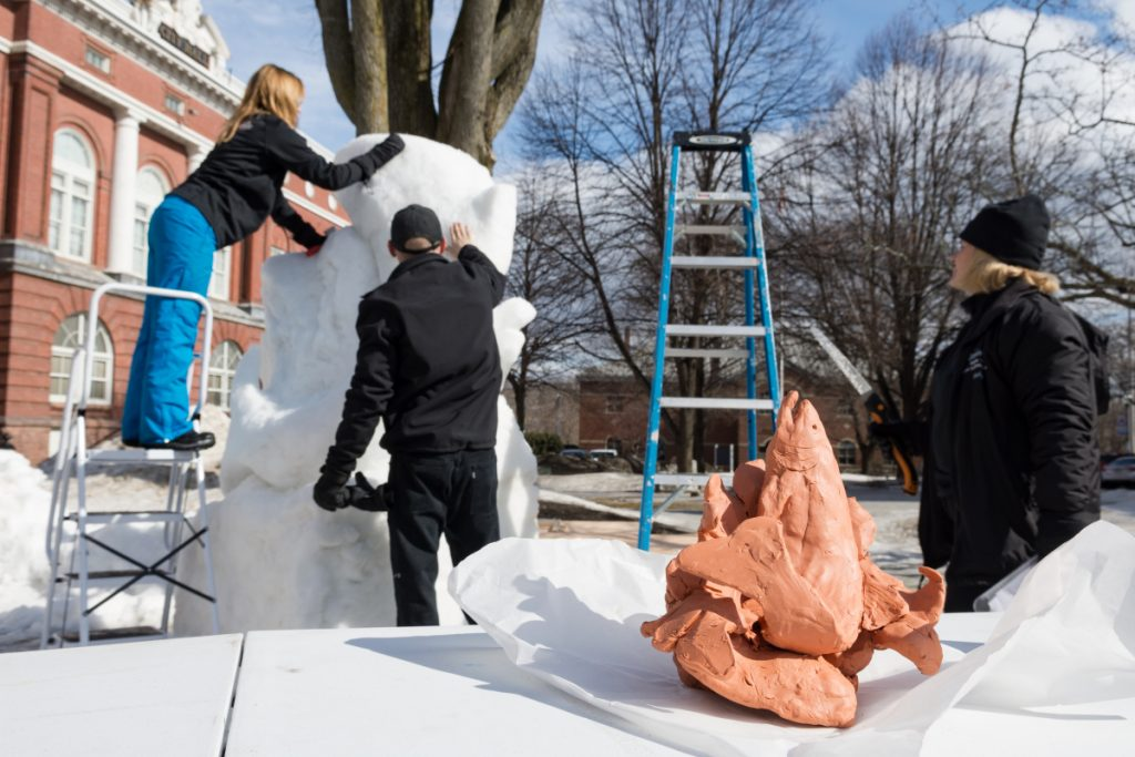 Starting from a clay model and a grid sketch, Cathy Thompson, right, watches as her children, Amanda Bolduc, left, and Chris Thompson carve a fish from a block of packed snow.