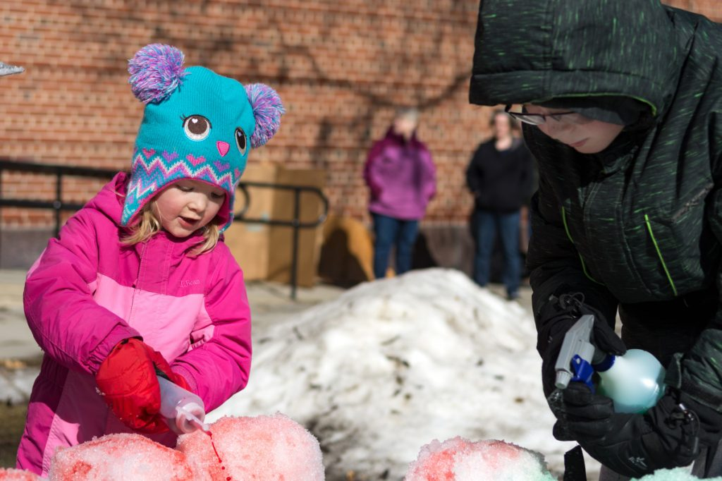Abigail Downie and her brother Jayden Downie, of Oakland, add color to a snow castle they carved out of a block of snow. The pair filled a large cardboard box with snow, packed it down, removed the box and then sculpted the castle Saturday afternoon in Castonguay Square in Waterville.