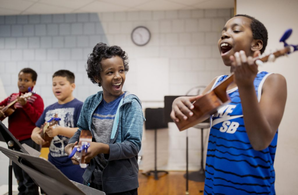 "Khalid Mahmed, 11,  and John Cubahiro, 9, center, practice before their concert. ""It's a very social, smile-inducing instrument,"" says camp director Lee Urban, owner of nearly 50 ukuleles."