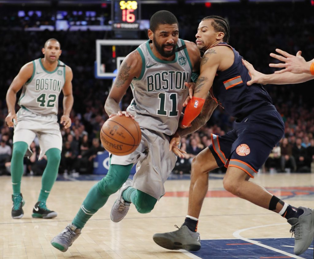 Boston guard Kyrie Irving drives past New York Knicks guard Trey Burke during the second half of Saturday's game in New York. Irving had 31 points to lead the Celtics in a 121-112 victory.