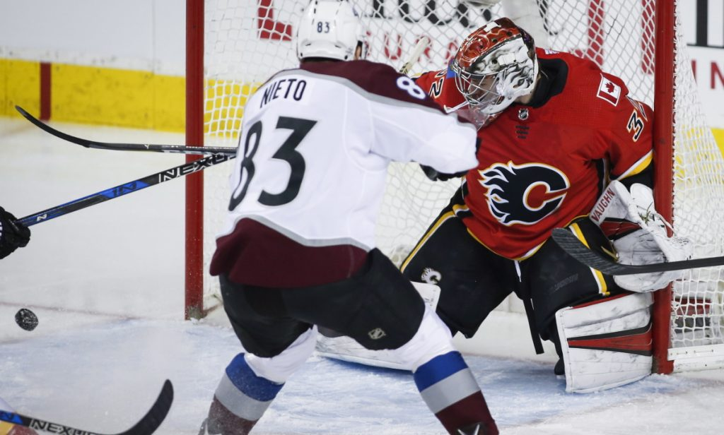 Jon Gillies, a goalie from South Portland recently called up by the Calgary Flames, turns aside a shot by Matt Nieto of the Colorado Avalanche during Calgary's 5-1 victory Saturday.