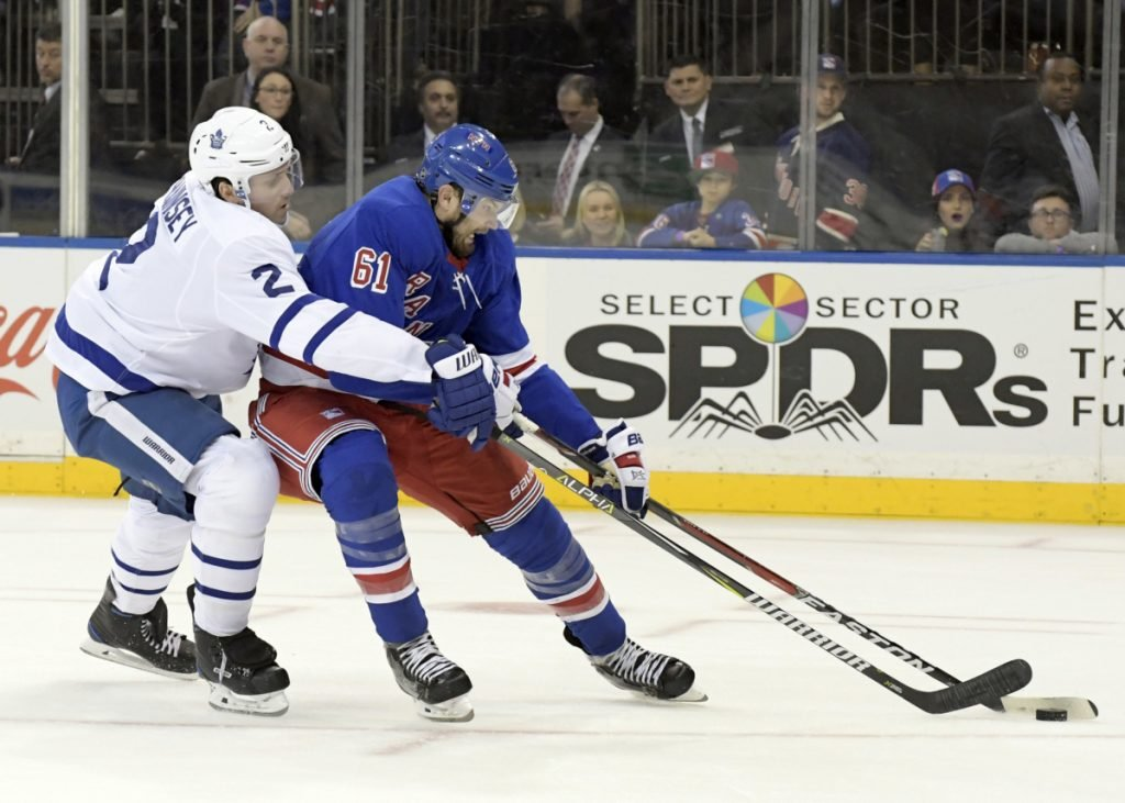 Toronto defenseman Ron Hainsey checks New York right wing Rick Nash as he controls the puck. The Rangers traded Nash as part of a multiplayer deal with the Bruins. New York acquired the Bruins' first-round pick in this year's draft as well as forwards Ryan Spooner and Matt Beleskey and a seventh-round pick in the 2019 draft.